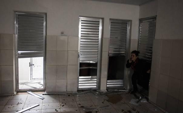 Imagem mostra mulher passando através de buraco de porta já destruída no Instituto Royal, em São Roque (SP)